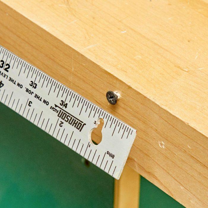 Organiser sa maison : accrochez une règle amovible à votre banc d'atelier.