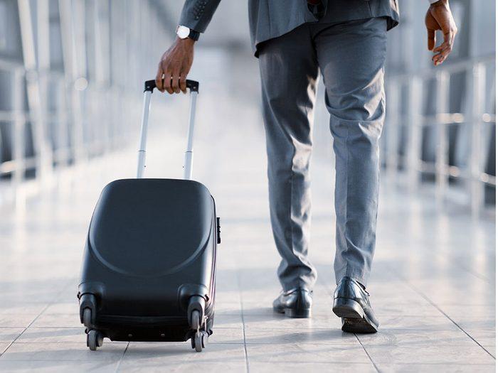 Rouler son bagage à main est un comportement impoli à éviter dans l'avion.