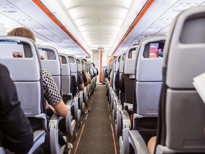 Prendre les accoudoirs est un comportement impoli à éviter en avion.