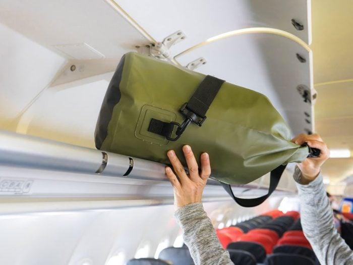 Monopoliser le porte-bagages est un comportement impoli à éviter en avion.