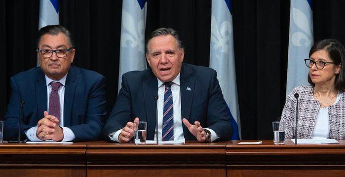 Le premier ministre du Québec, François Legault, entouré du directeur national de la santé publique du Québec, Horacio Arruda et de la ministre de la Santé du Québec, Danielle McCann, lors de leur premier point de presse annonçant des mesures pour contenir le virus COVID-19, le 12 mars à l'Assemblée législative de Québec.