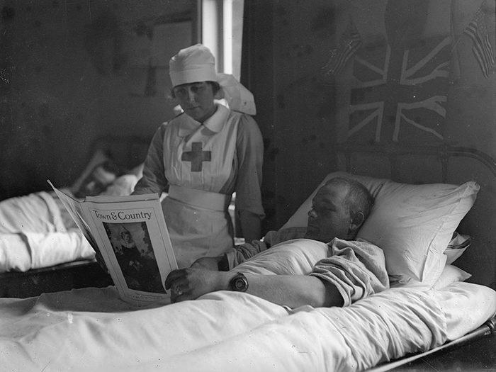 Une infirmière et son patient en pleine lecture.