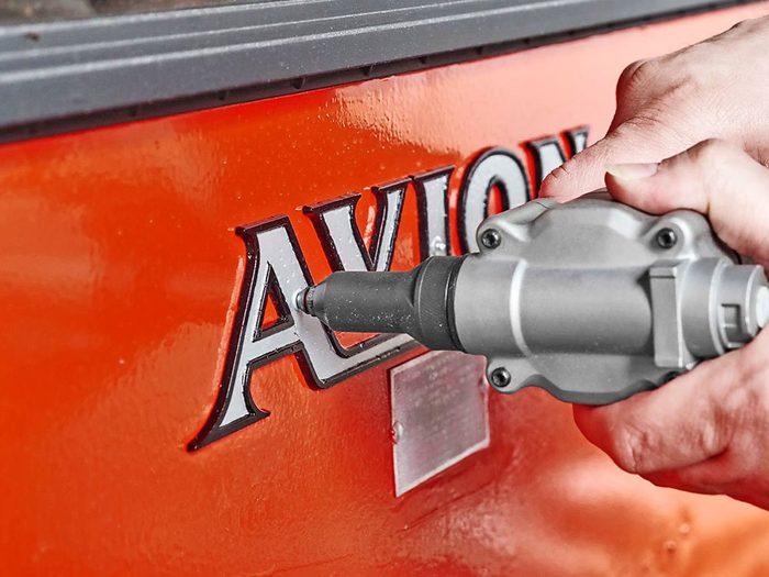 Installation des plaques signalétiques et des pièces décoratives sur la caravane rétro.