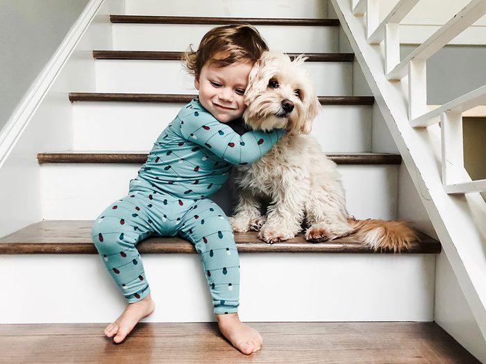 Un beau duo chien et bébé dans l'escalier.