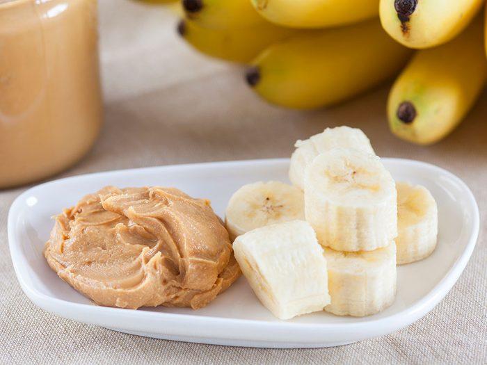 Manger du beurre d'arachide et banane pour un déjeuner santé.