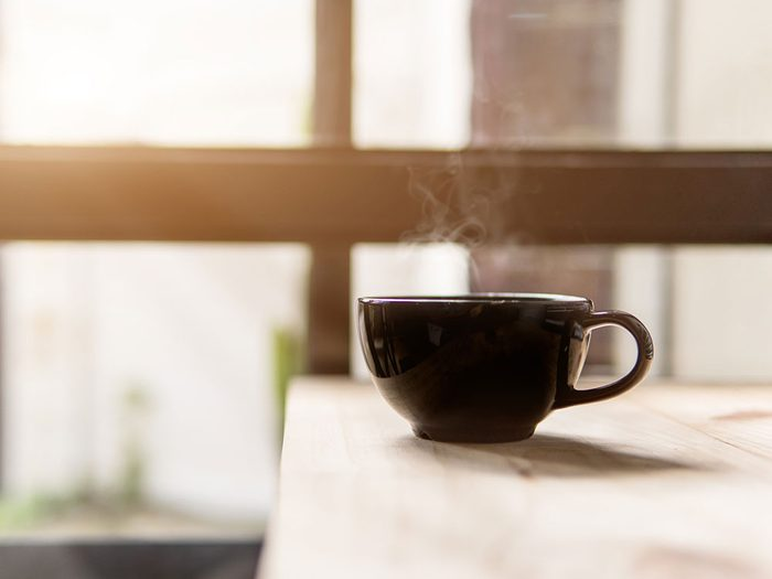 Boire du thé noir à l'huile de coco et au miel pour un déjeuner santé.