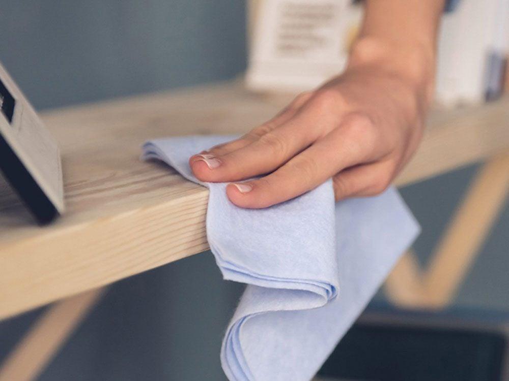Épousseter les surfaces pour entretenir la maison.