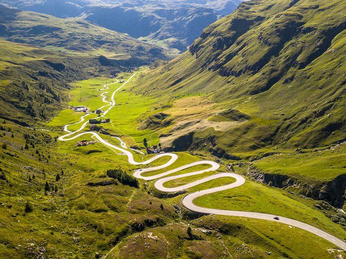 Photo aérienne de drone d'un chemin serpentant les Alpes suisses.
