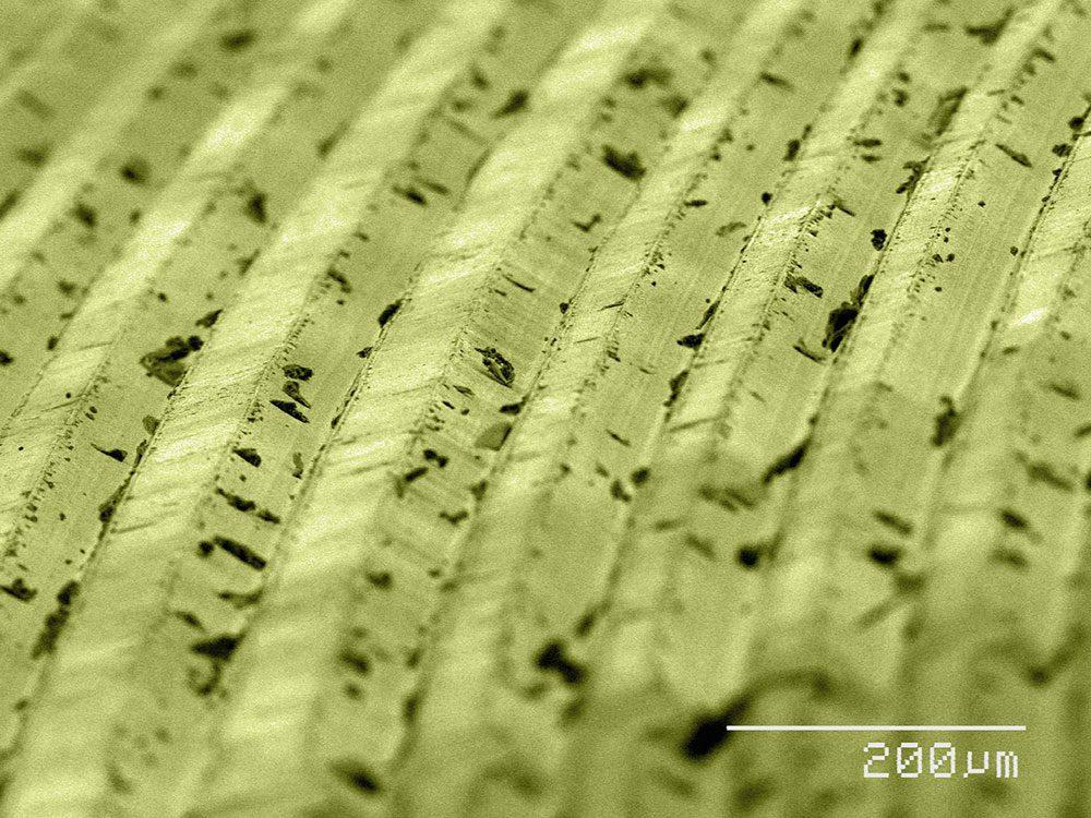 Des sillons sur un disque vinyle en image au microscope.
