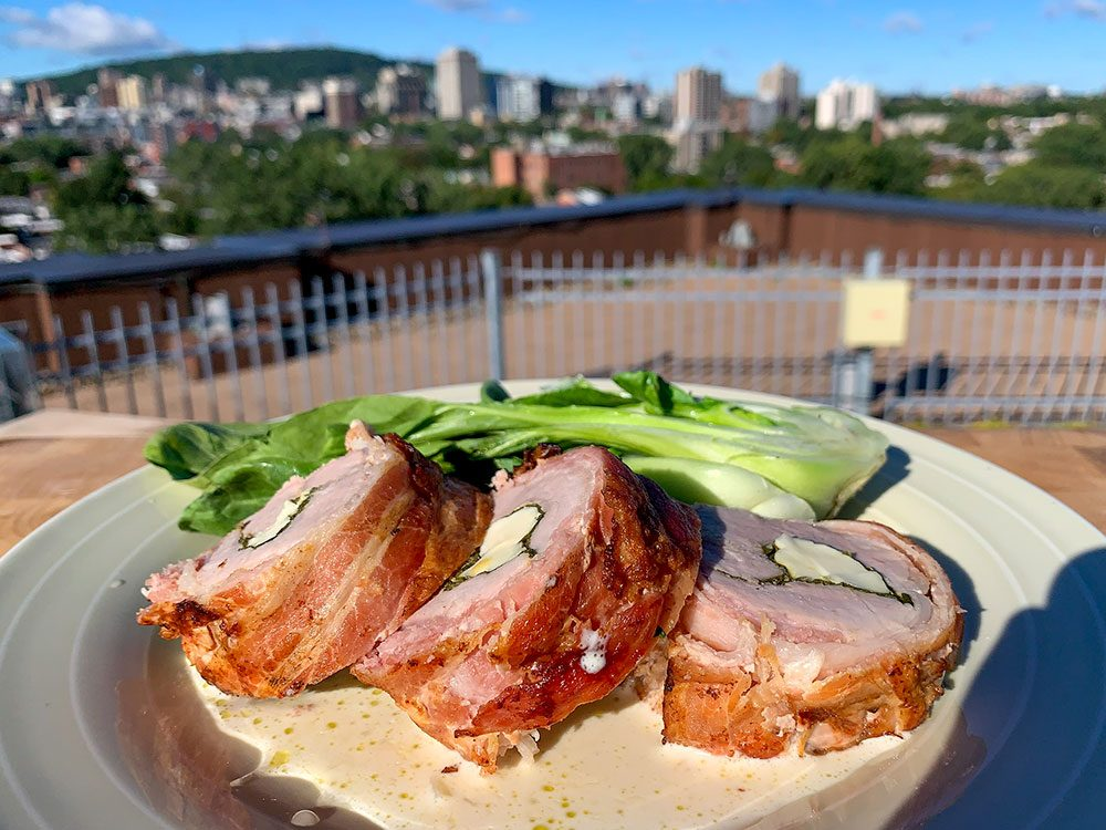 Filet de porc farci et enroulé de bacon, sauce crème infusée au romarin.