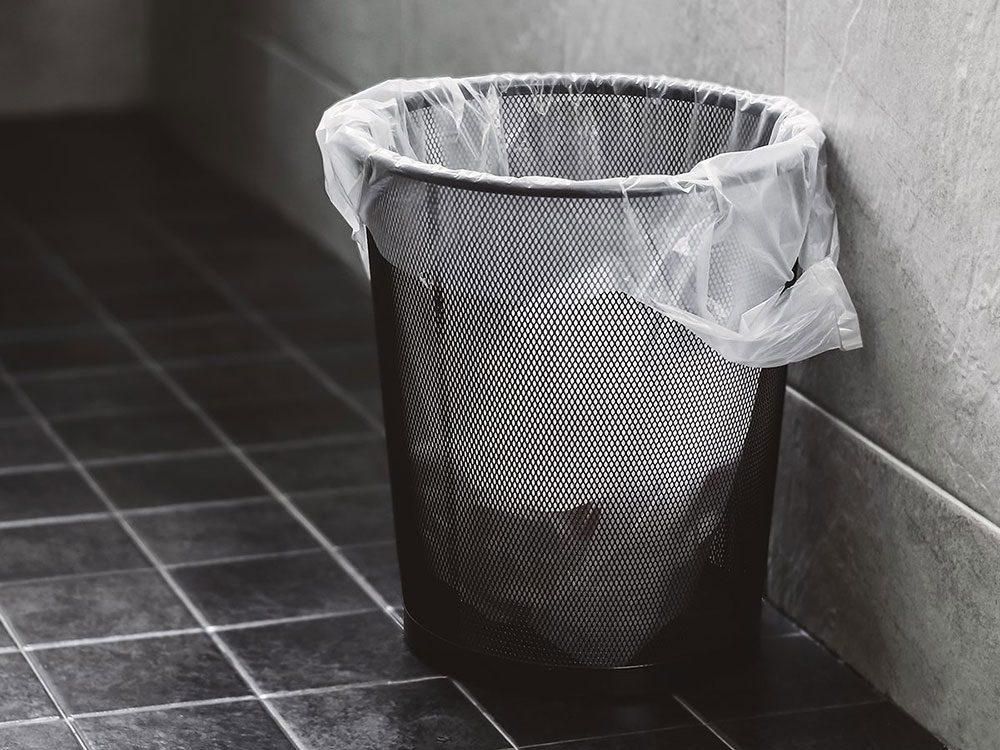 Tapisser une petite poubelle avec les sacs de plastique.