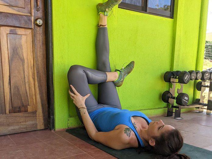 La posture de yoga de la forme du 4 au mur.