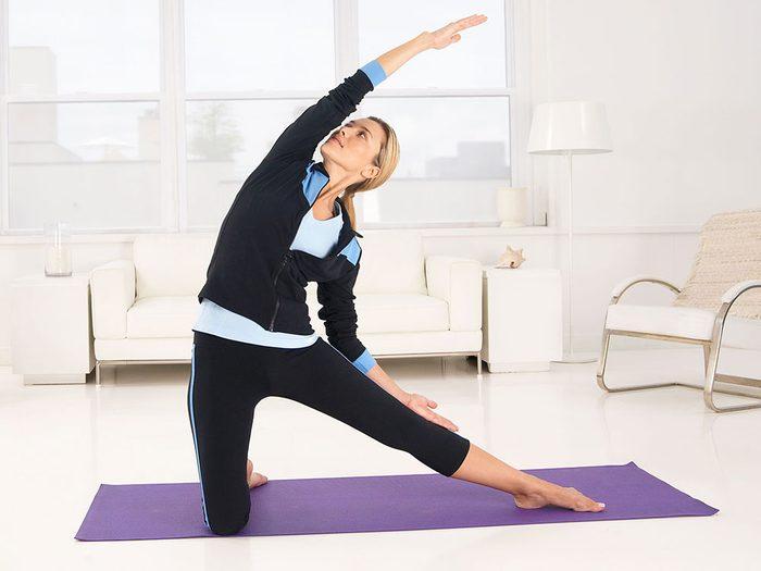 Entrainement de yoga avec le genou pointé vers le plafond.
