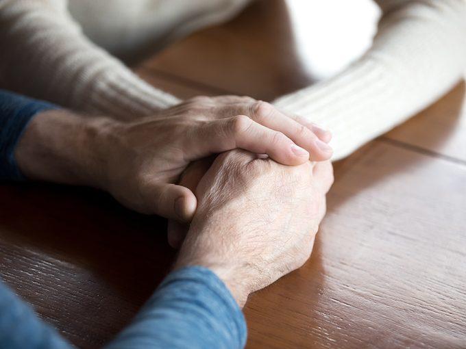 Un couple se touche les mains pour du réconfort.