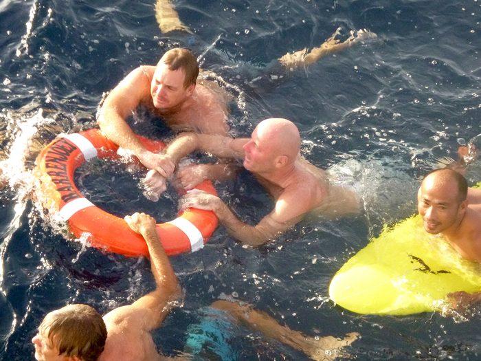 Une bouée de sauvetage est lancée par la balustrade et des silhouettes plongent du bateau pour sauver l'eau qui était perdu en mer.